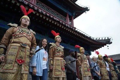 Foreign friends taking photos with popular warriors in golden armor at the city wall of Xi'an